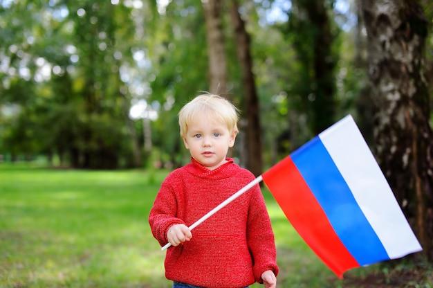 Netter kleinkindjunge, der draußen russische flagge hält