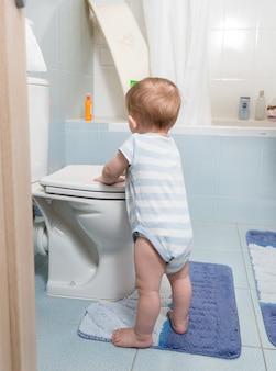Netter kleinkindjunge, der im badezimmer steht und mit toilette spielt
