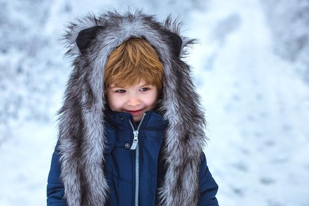 Netter kleinkindjunge, der im winterpark im schnee draußen spielt junge träumt von der winterzeit, die gut gekleidet...