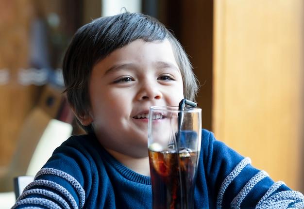 Netter kleinkindjunge, der kaltes getränk trinkt