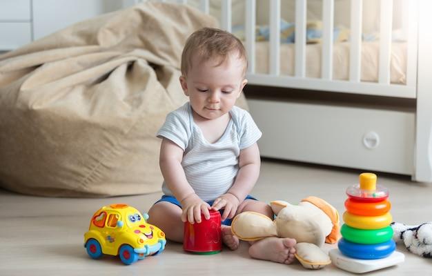 Netter kleinkindjunge, der mit buntem spielzeug auf dem boden im wohnzimmer spielt