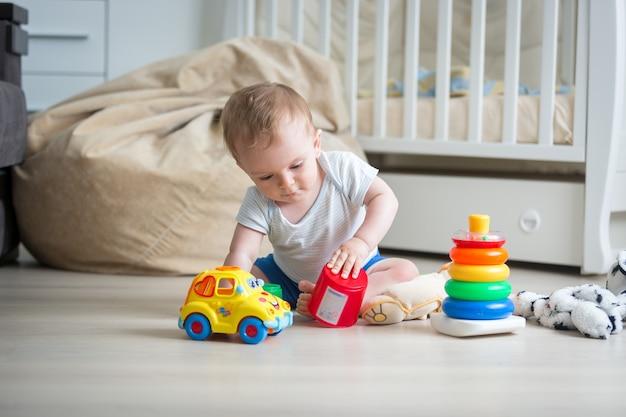 Netter kleinkindjunge, der mit spielzeug auf dem boden spielt