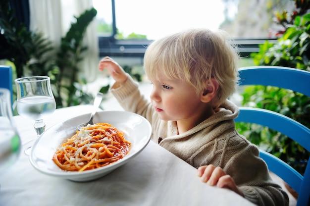 Netter kleinkindjunge, der zuhause teigwaren im italienischen restaurant isst. gesundes / ungesundes essen für kleine kinder