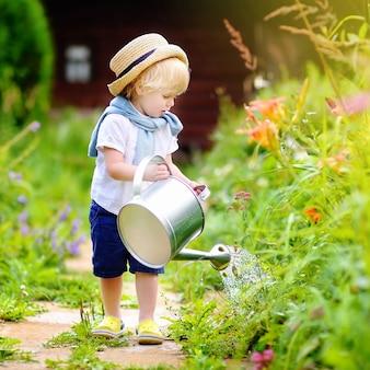 Netter kleinkindjunge in den strohhutbewässerungsanlagen im garten am sonnigen tag des sommers