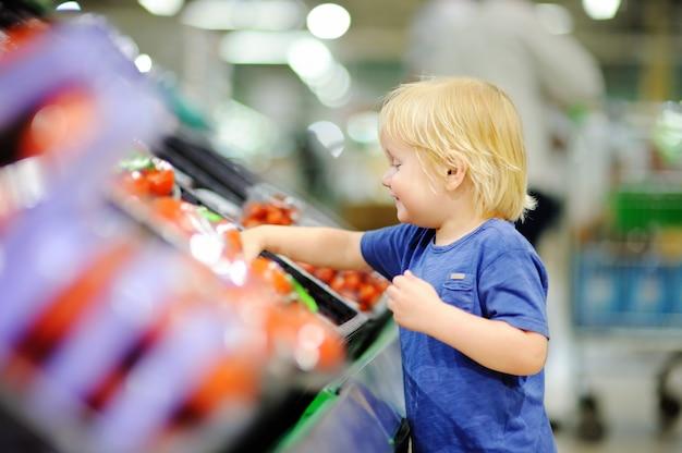 Netter kleinkindjunge in einem lebensmittelgeschäft oder in einem supermarkt, die frische tomaten wählen. gesunder lebensstil für junge familien mit kindern