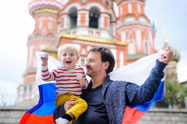 Netter kleinkindjunge und sein mittelaltervater, die russische flagge mit der kathedrale des heilig-basilikums hält