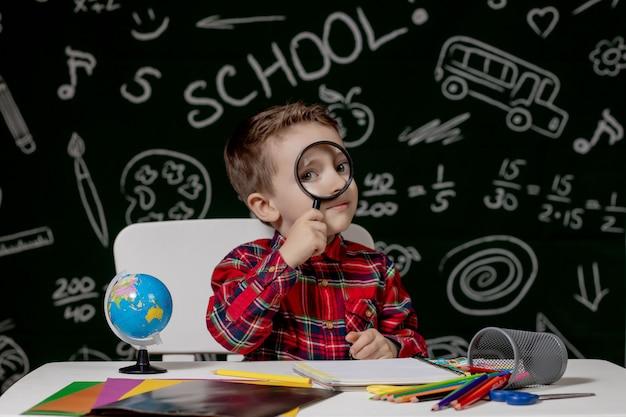 Netter kluger junge sitzt an einem schreibtisch mit lupe in der hand. kind liest ein buch mit einer tafel auf einem hintergrund. fertig für die schule. zurück zur schule