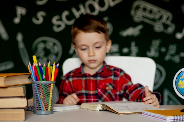 Netter kluger junge sitzt an einem schreibtisch mit lupe in der hand. kind liest ein buch mit einer tafel. fertig für die schule. zurück zur schule