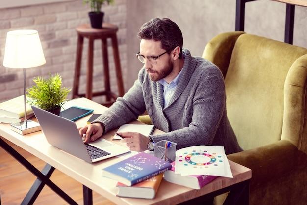 Netter kluger mann, der den knopf auf seinem laptop drückt, während er vor dem laptopbildschirm sitzt