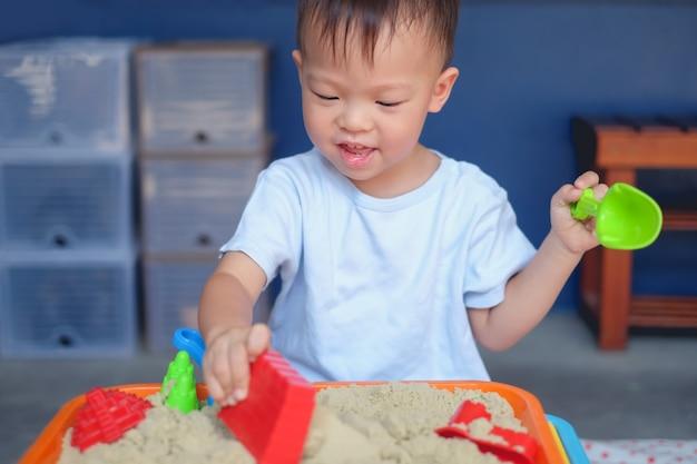 Netter lächelnder asiat 2 jahre alter kleinkindjunge, der zu hause mit kinetischem sand im sandkasten / in der kindertagesstätte / in der tagespflege spielt