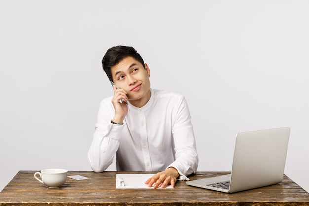 Netter lächelnder asiatischer junger unternehmer, der am telefon im büro spricht