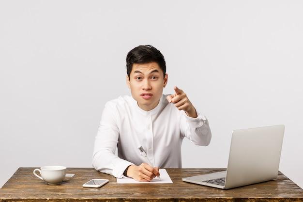 Netter lächelnder asiatischer junger unternehmer, der auf das büro zeigt