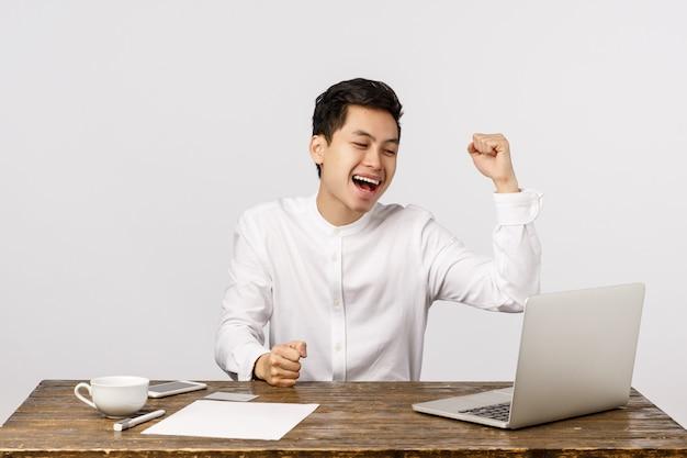 Netter lächelnder asiatischer junger unternehmer, der im büro feiert