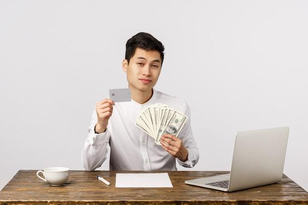 Netter lächelnder asiatischer junger unternehmer, der kreditkarte und geld im büro hält