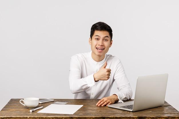 Netter lächelnder asiatischer junger unternehmer im büro, das sich daumen zeigt