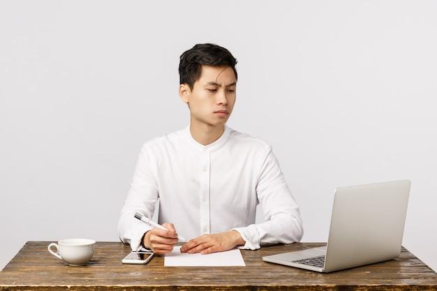 Netter lächelnder asiatischer junger unternehmer im büro