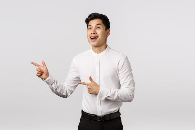 Netter lächelnder asiatischer junger unternehmer mit weißem hemd zeigend auf die seite