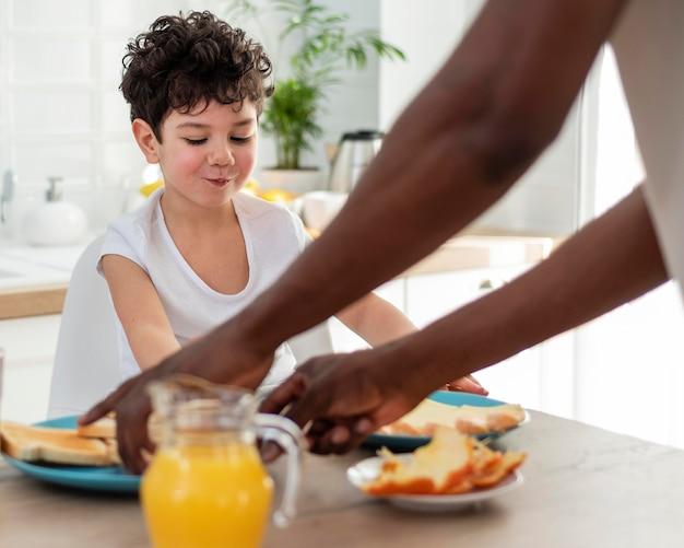 Netter lächelnder junge, der frühstück mit seinem vater hat