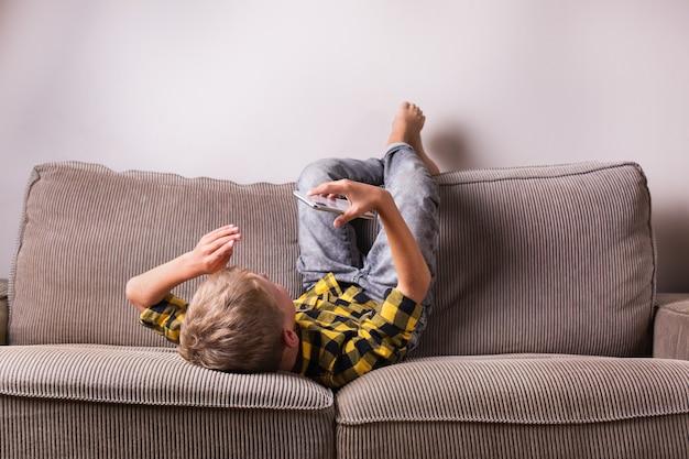 Netter lächelnder junge, der mit familie und freunden spricht, videoanrufe am telefon macht, auf einer couch sitzt. bleiben sie zu hause, sperren, soziale distanzierung, quarantäne.
