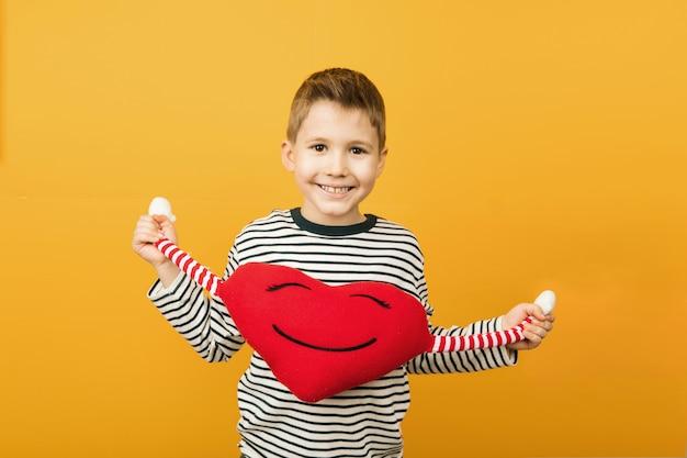 Netter lächelnder junge, der rotes herzspielzeug in ihren händen lokalisiert hält. valentinstagskonzept. studioaufnahmen.