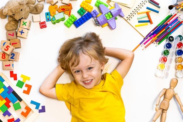 Netter lächelnder junge der vorschule zeichnen und spielen mit blöcken, flugzeug und autos.