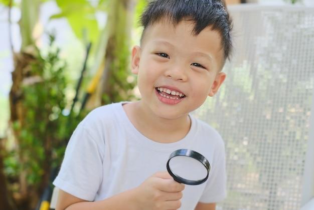 Netter lächelnder kindergartenjunge, der die umgebung erforscht, indem er durch eine lupe im garten schaut