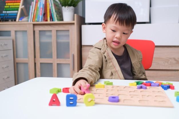 Netter lächelnder kindergartenjunge, der mit alphabetblöcken spielt, asiatische kinder, die englisch mit hölzernem pädagogischem abc-spielzeugrätsel lernen