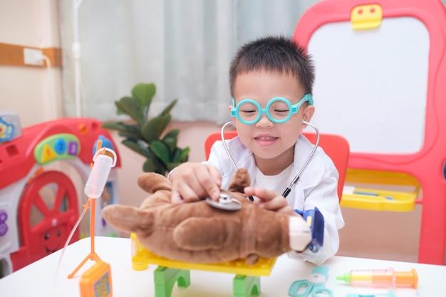 Netter lächelnder kleiner asiatischer 3 - 4 jahre alter kleinkindjunge in arztuniform, der spaß hat, arzt zu spielen