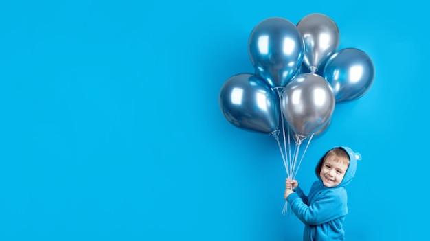 Netter lächelnder kleiner junge, der mit luftballons lokalisiert auf blauem hintergrund aufwirft. kindergeburtstagsfeierkonzept. alles gute zum geburtstag banner