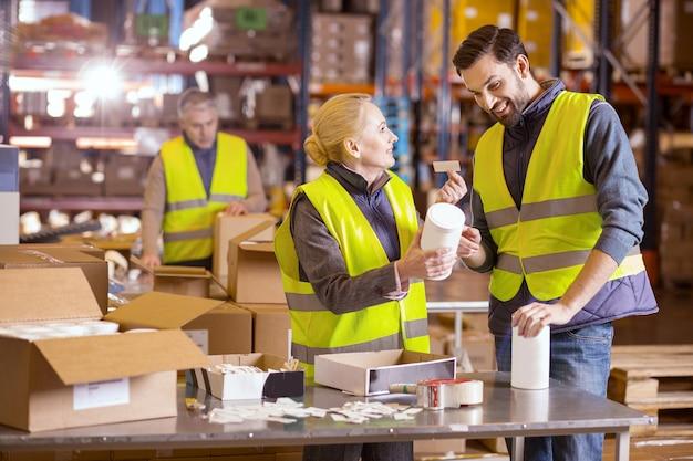 Netter lagerarbeiter, der lächelt und einander ansieht, während etiketten auf den produkten angebracht werden