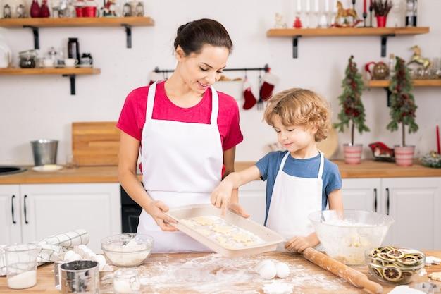 Netter lockiger junge, der auf eines der kekse auf tablett zeigt, während er seine form mit mutter in der küche bespricht