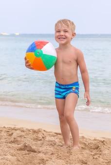 Netter lustiger glücklicher kleiner junge, der in den wasserwellen am seeozean an einem sonnigen tag spielt