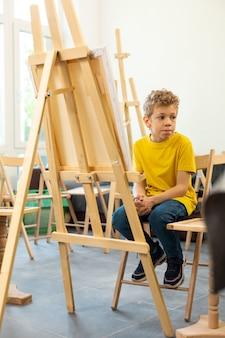 Netter lustiger junge, der gelbes t-shirt trägt, das in der kunstschule sitzt