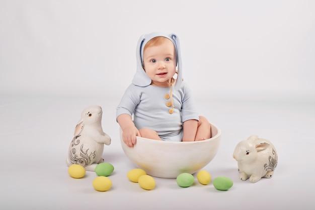 Netter lustiger junge mit hasenohren und bunten ostereiern und kaninchen. ostern baby. gruß osterkartenschablone.