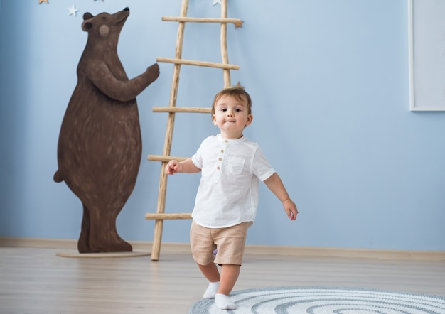 Netter lustiger kleiner junge, der läuft, spaß hat und in seinem kinderzimmer spielt