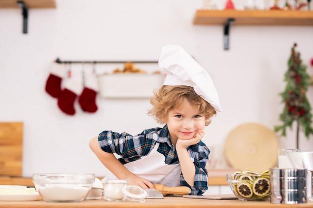 Netter lustiger kleiner junge in der schürze und in der kochmütze, die nudelholz halten und sie betrachten, während sie durch küchentisch mit zutaten für kekse stehen