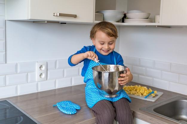 Netter lustiger kleinkindjunge, der apfelkuchen in der häuslichen küche backt