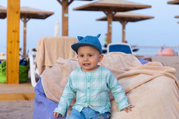 Netter lustiger kleinkindjunge, der auf dem strandtuch an der entspannungszone in einem tropischen resort sitzt, das beiseite schaut, kleinkind mit kleidern, die im sand schmutzig sind.
