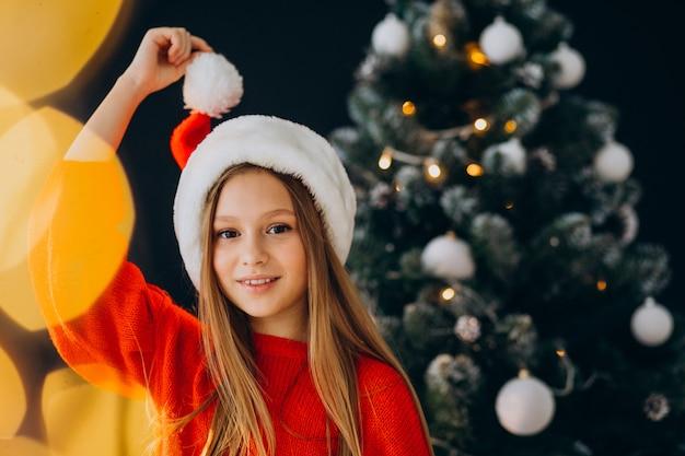 Netter mädchenjugendlicher im roten weihnachtsmannhut durch weihnachtsbaum