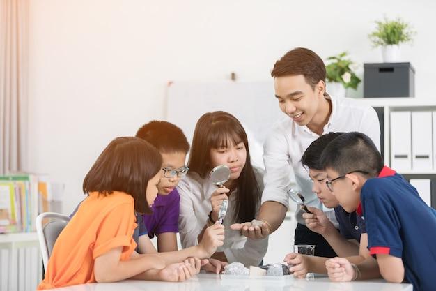 Netter männlicher lehrer, der etwas zu einer gruppe junger studenten erklärt