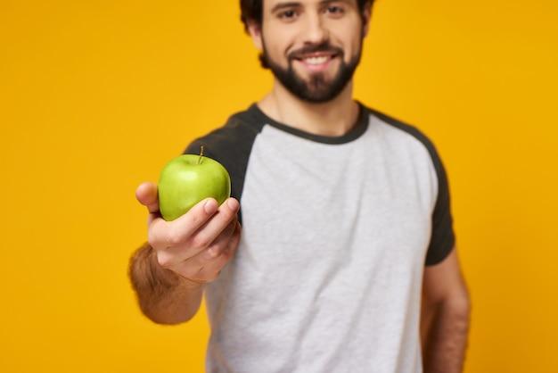 Netter mann bietet grünen apfel an. vegetarismus.
