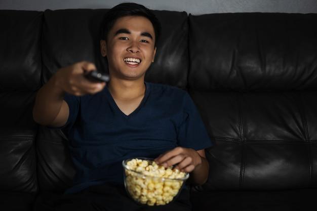 Netter mann, der fernbedienung hält und fernsieht beim sitzen auf sofa nachts