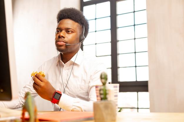 Netter mann, der seine kopfhörer bei der arbeit im callcenter trägt
