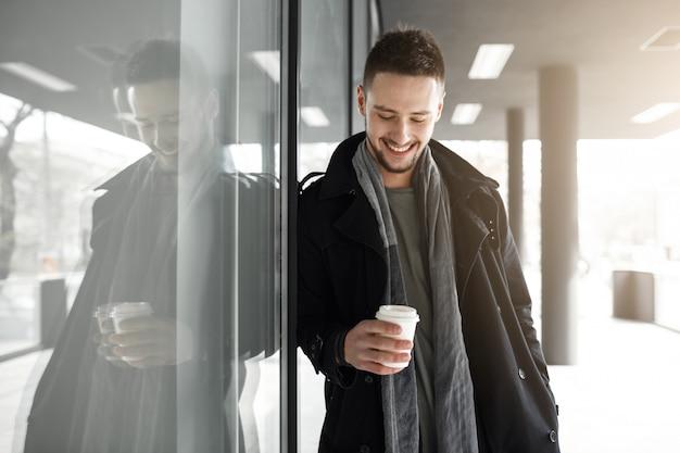 Netter mann im schwarzen mantel, der weißen pappbecher hält.