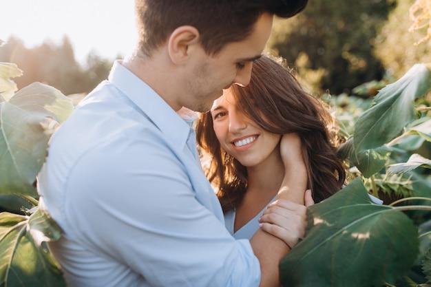 Netter mann und schwangere frau umarmen sich zarte stellung auf dem gebiet