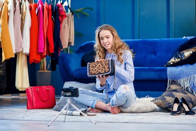 Netter modeblogger, der der kamera handtasche präsentiert.