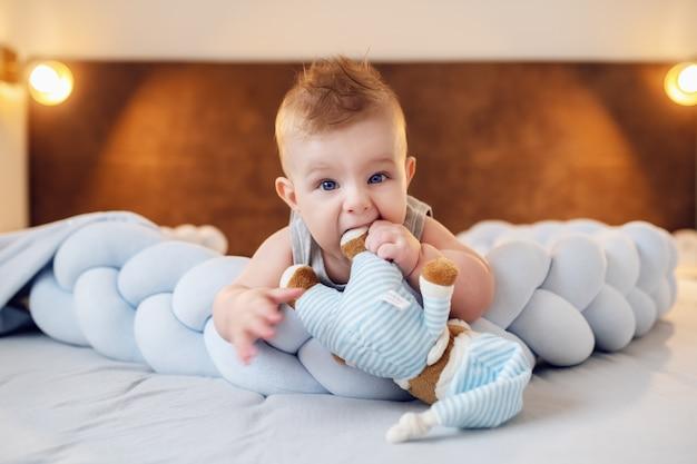 Netter molliger kaukasischer kleiner junge, der auf bauch auf bett im schlafzimmer liegt und teddybär kaut. der erste zahn ist fast da.