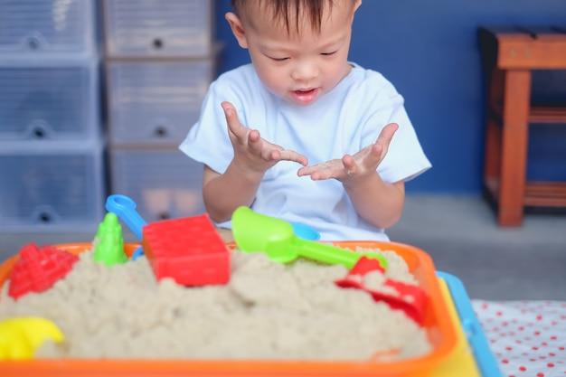 Netter neugieriger asiat 2 jahre alter kleinkindjunge, der zu hause mit kinetischem sand im sandkasten / in der kindertagesstätte / in der tagespflege spielt