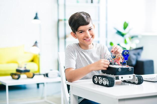 Netter optimistischer kleiner junge, der roboter baut, während er sich auf den ingenieurunterricht vorbereitet