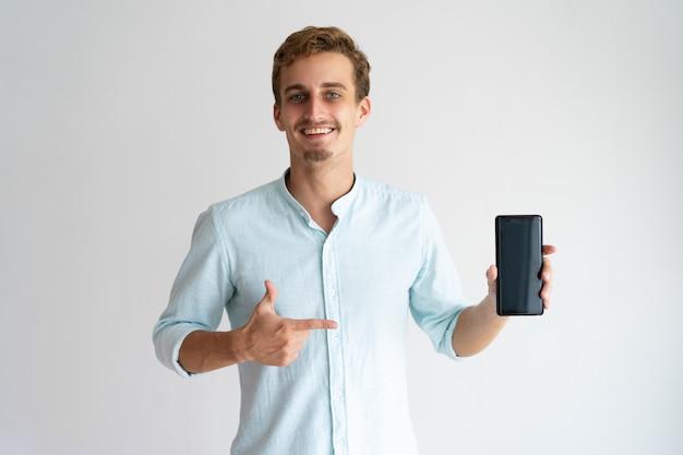 Netter optimistischer verkaufsleiter, der neuen smartphone vorführt.